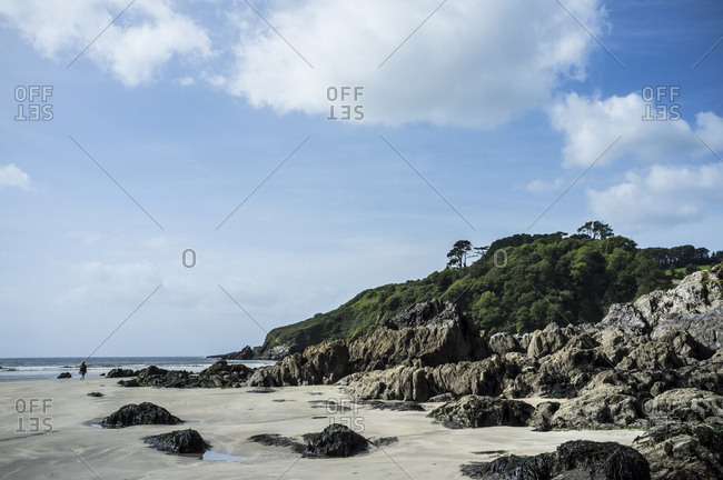 The headland and rocks on a sandy beach on the coastline under a blue sky with light cloud. A single person walking.