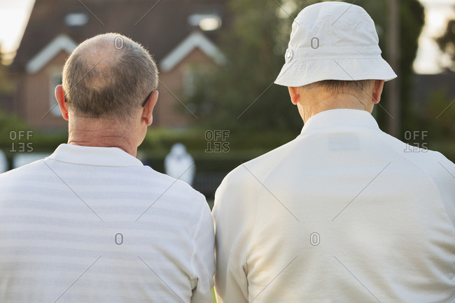 Two companions, two men standing side by side in white shirts outdoors. Lawn bowls players, one in a sun hat.