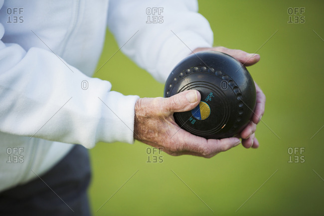 A man holding a black wooden lawn bowls ball in his hands. Notches and grooves in the surface.