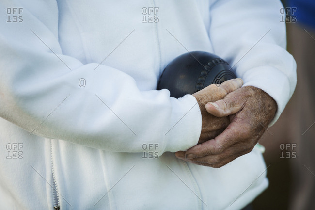 A man holding a black wooden lawn bowls ball in his hands close to his chest.