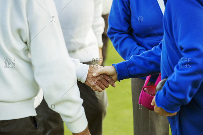 Two teams, four people shaking hands before or after a sporting match.