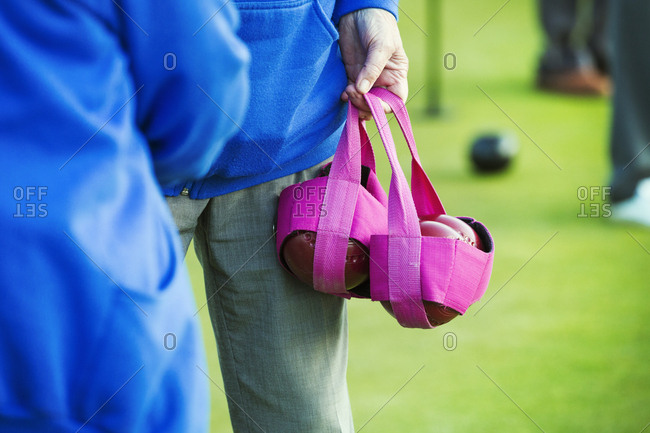 Two people in blue shirts, one carrying four wooden lawn bowls in a pink bag.