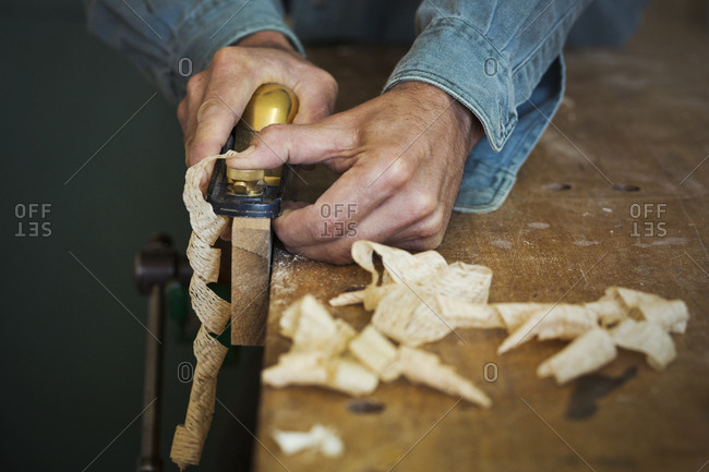 A craftsman holding a spokeshave and using it to shape a piece of wood in a clamp.