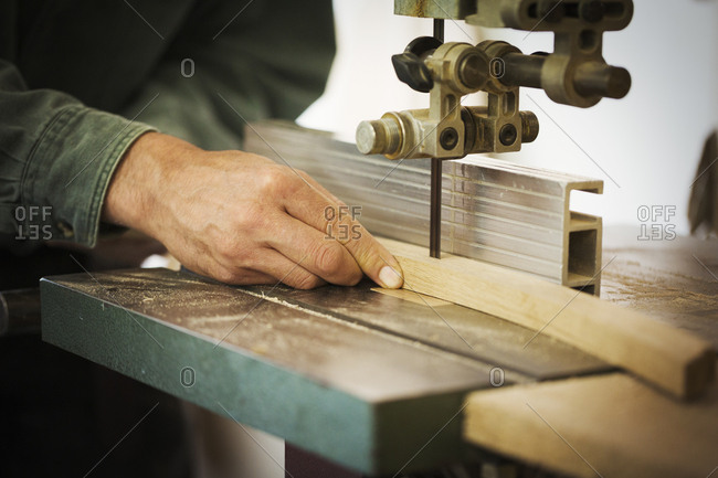 A craftsman using a machine drill on a piece of smooth planed shaped wood.
