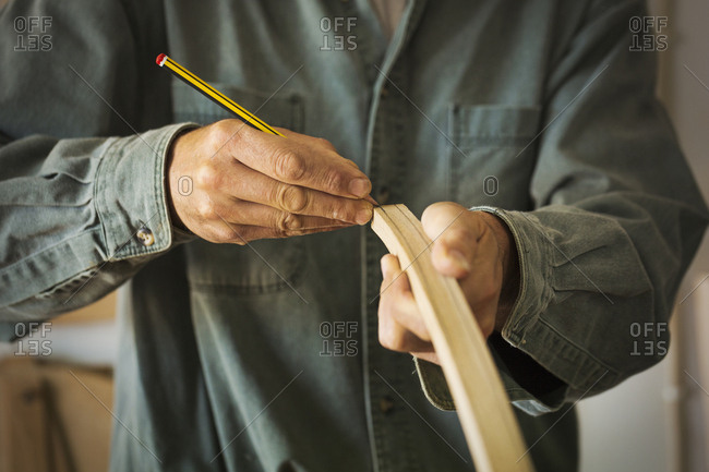 A craftsman using a pencil and marking a piece of curved wood.