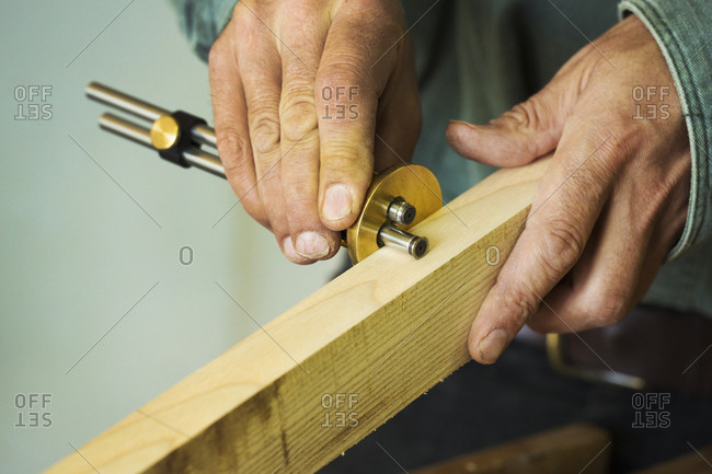A craftsman using a measuring gauge on a piece of fresh wood.