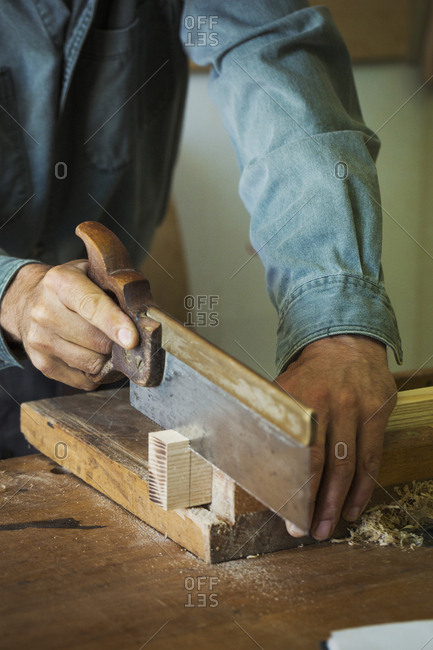 A craftsman using a handsaw on a piece of wood.