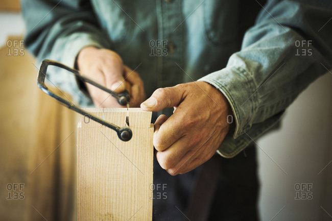 A man using a handsaw on a piece of wood.