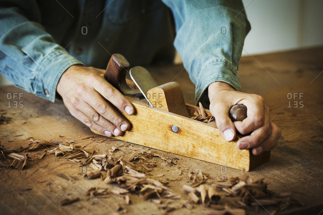 A workman using a hand wood plane on the surface of a large piece of wood.