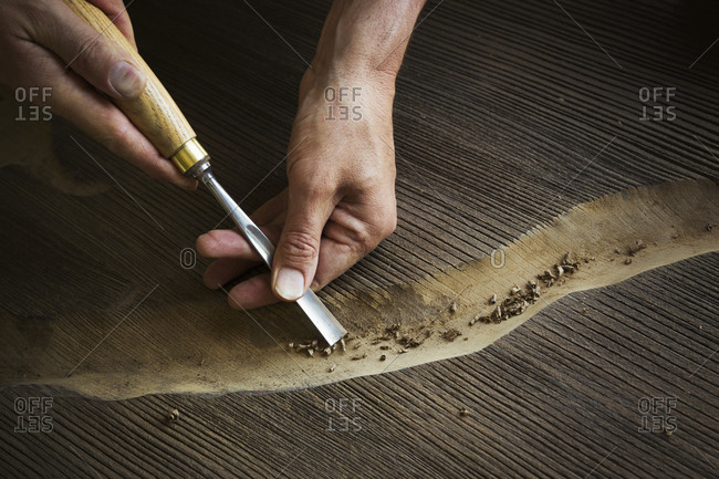 A craftsman using a chisel to carve out a deep groove in a piece of wood.