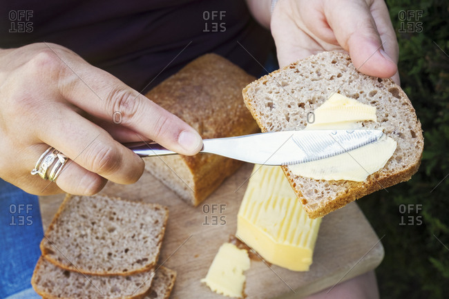 A person buttering bread with a knife, food preparation.