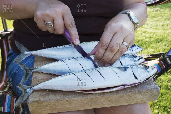 A woman scoring the skin of three fresh mackerel fish on the slab being prepared for cooking.