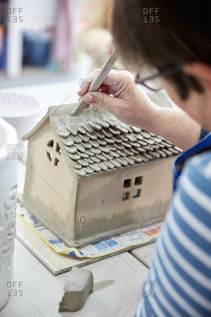A woman potter using a small shaping tool to create the roof details for a clay model of a house.