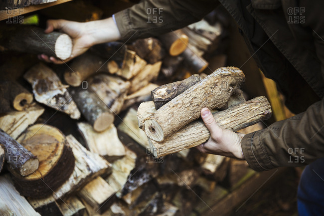 A man stacking logs, wood of different lengths. A firewood store.