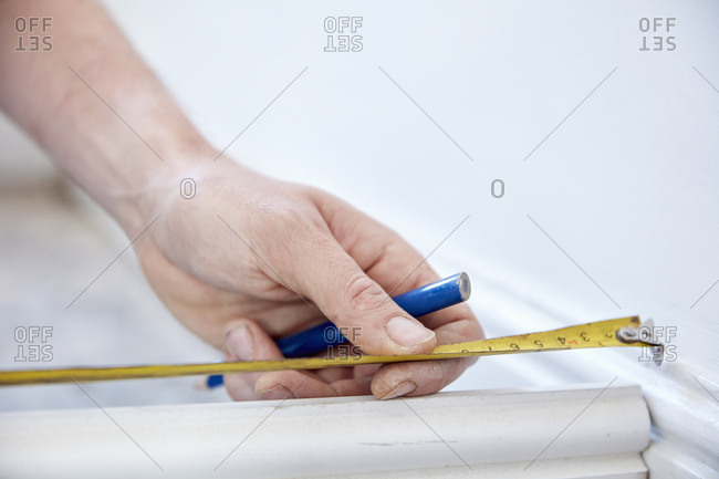 A man using a steel measuring tape, to measure, holding a small pencil.