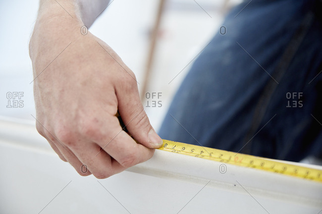 A man using a steel measuring tape.