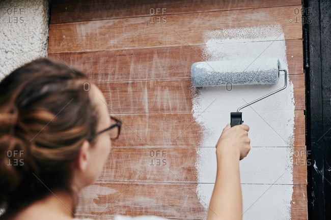 A woman using a paint roller, painting wooden planks on a wall.