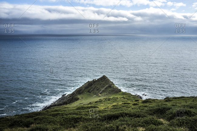 The view from above of a sharp ridge and steep hillside on a headland reaching into the sea. Waves breaking under a cloudy sky.