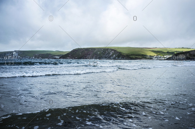 View of wave patterns in shallow choppy water, from the sea shore. Headland and coastline.