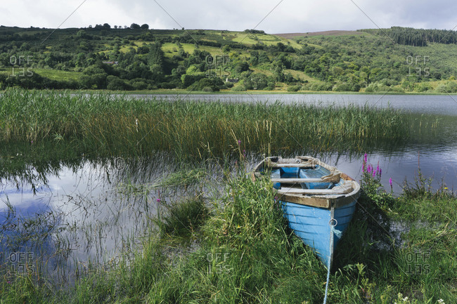 Blue wooden rowboat lying on the shore of Glenade Lake, Glenade, County Leitrim, Ireland.