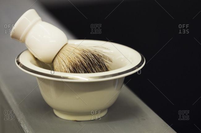 A traditional ceramic shaving bowl and shaving brush.