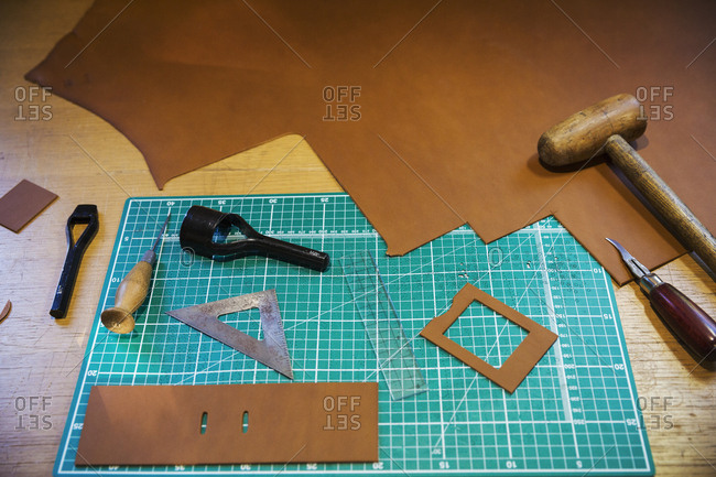 Workbench and cutting mat with a large smooth piece of brown leather, and tools for measuring cutting and stitching, leatherworking  tools.