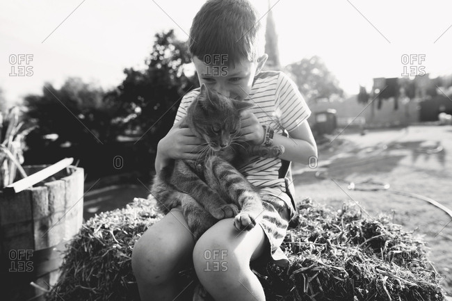 Child playing outdoors with a cat