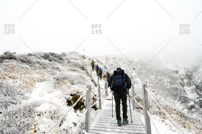 Hikers on snow covered footpath ascending Hallasan on Jeju Island