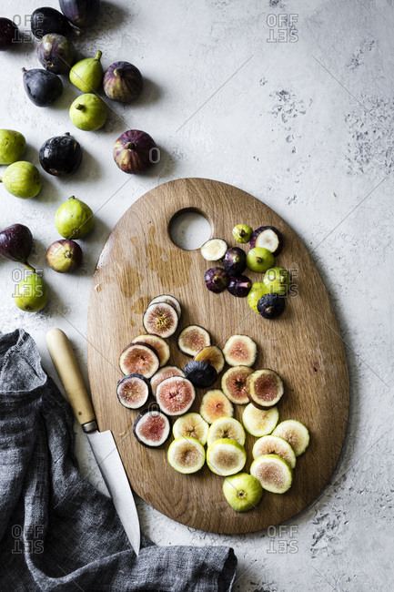 Fresh figs on a chopping board, being prepared for cooking