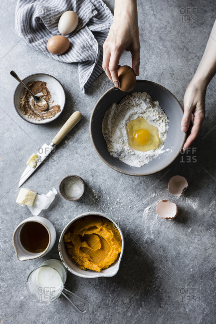 A woman baking in a kitchen, mixing eggs and flour