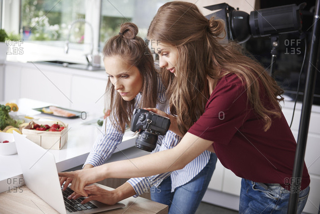 Bloggers using laptop and camera in kitchen