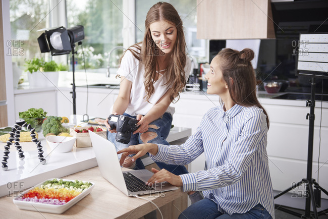 Two food bloggers using laptop and camera in kitchen