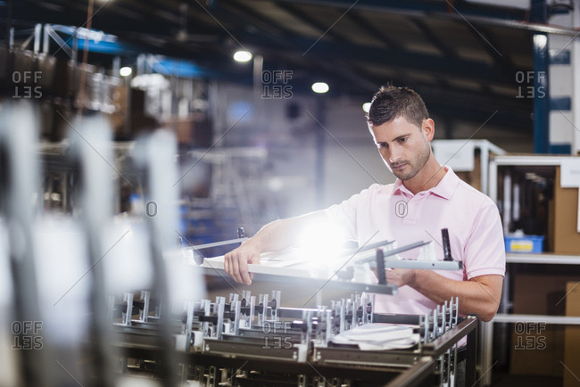Businessman standing in shop floor- testing products