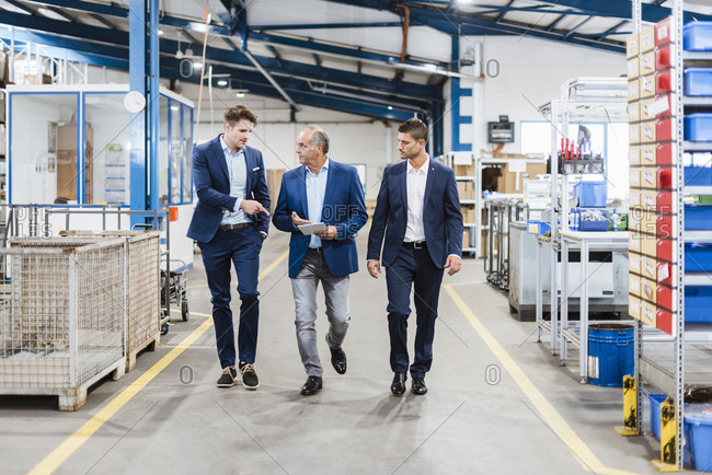 Three businessmen walking through shop floor- discussing decisions