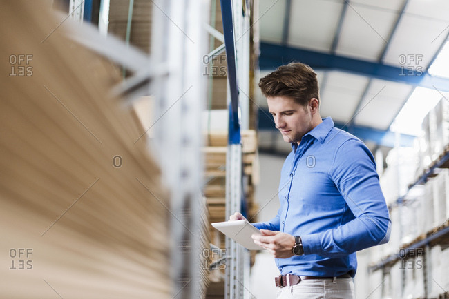 Young man working in warehouse- using digital tablet stock