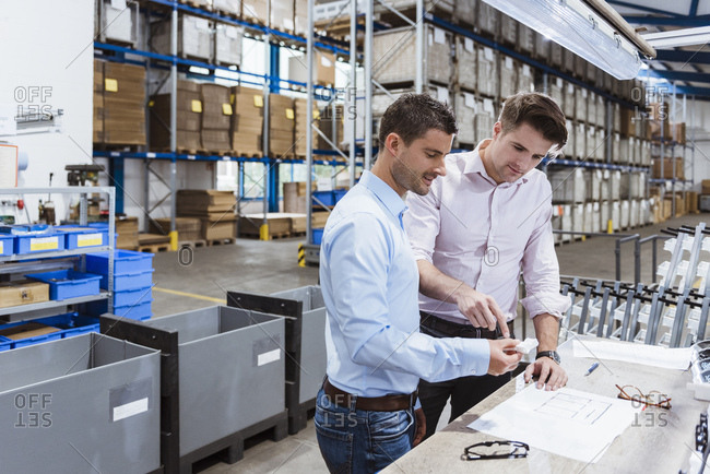 Business people standing on shop floor- discussing product improvement