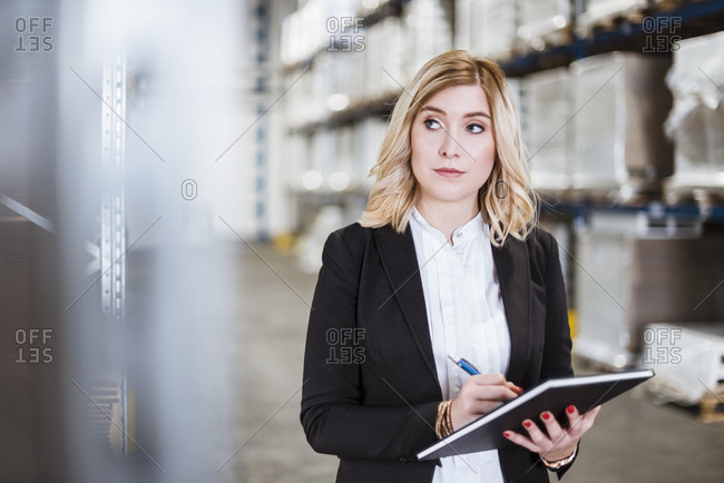 Blond businesswoman standing in storehouse- writing in notebook