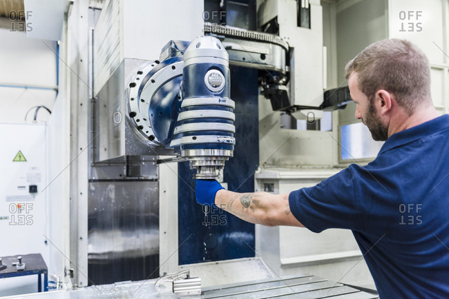 Man working on machine in industrial factory