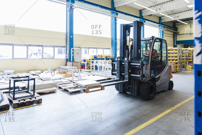 Man on forklift in factory warehouse