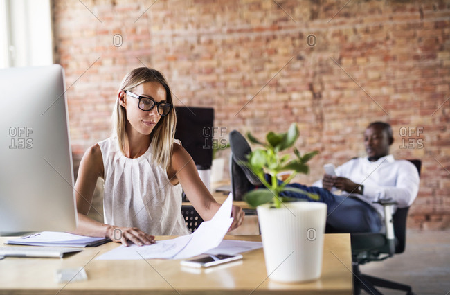 Businesswoman working at desk in office with colleague in background