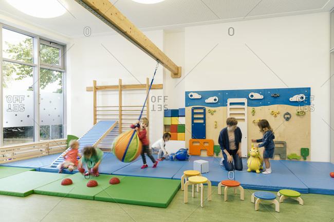 Pre-school teacher and children in gym room in kindergarten