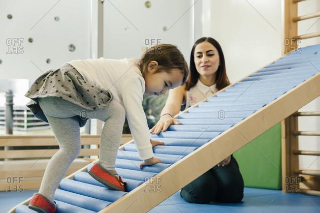 Pre-school teacher watching little girl walking upwards