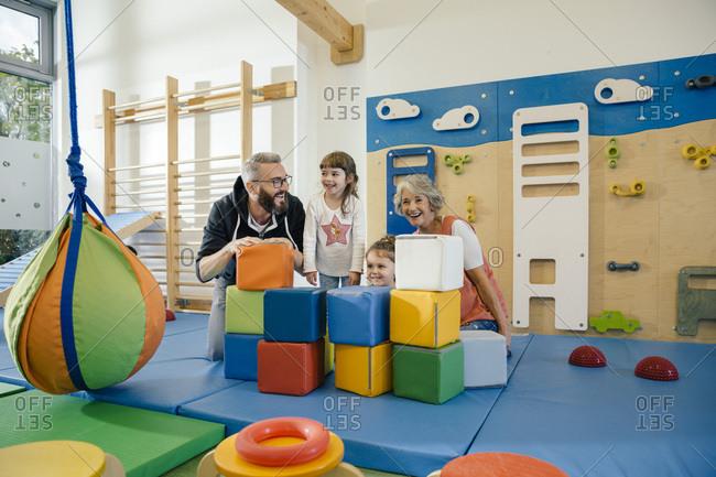 Happy children and teachers in gym room in kindergarten