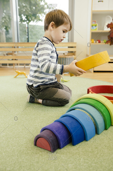 Boy playing with wooden rainbow shapes in kindergarten