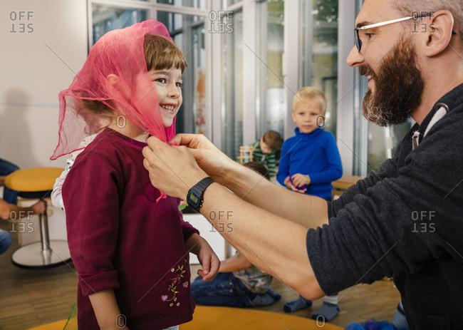 Pre-school teacher binding headscarf for girl in kindergarten