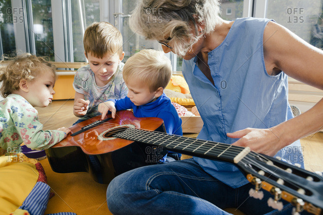 Pre-school teacher showing a guitar to children in kindergarten