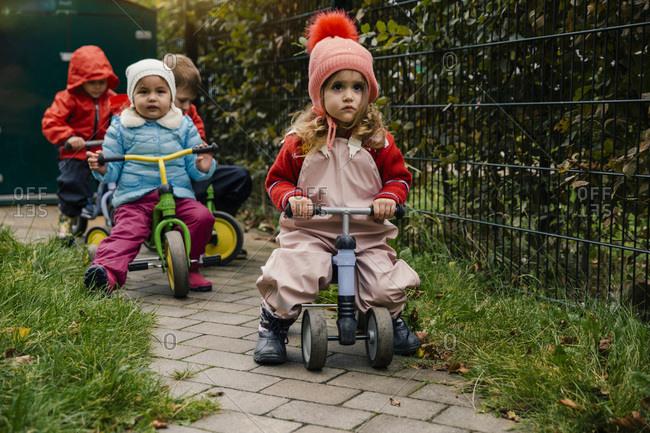 Children using scooters in garden of a kindergarten