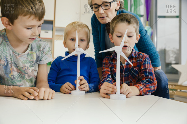 Boys and pre-school teacher looking at wind turbine models in kindergarten