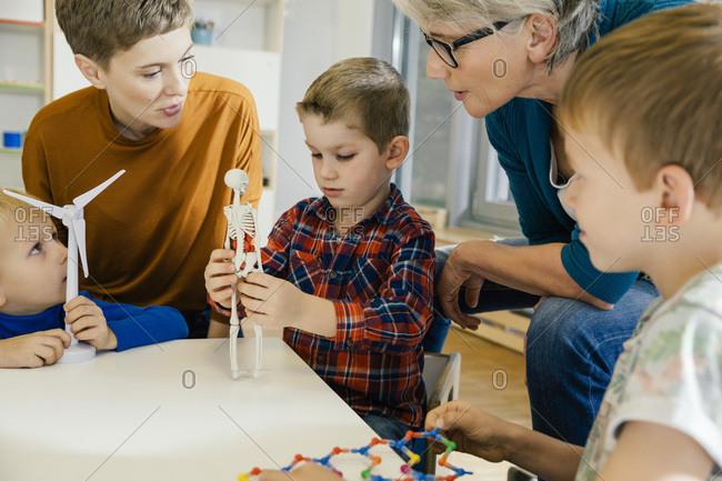 Children and pre-school teachers with wind turbine and anatomical model in kindergarten