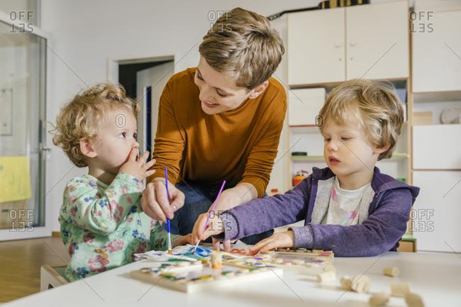 Pre-school teacher painting with two children in kindergarten